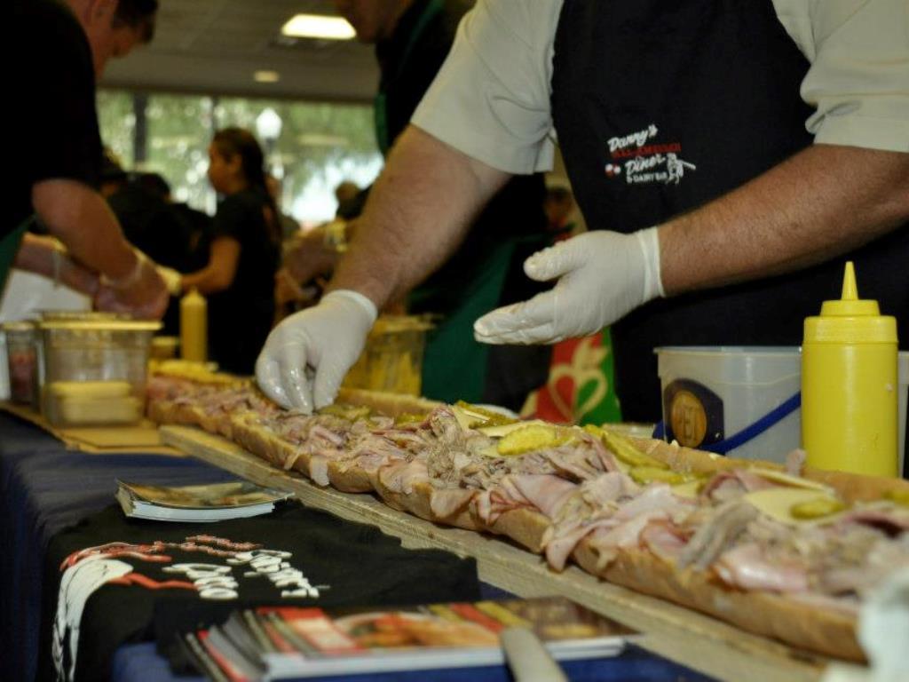man preparing long row of cuban sandwiches
